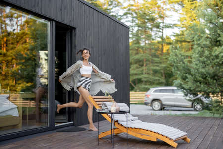 Young woman runs out of the house on wooden terrace with pine forest view. Concept of solitude and recreation on nature. Wellness and mindful resort. Beautiful quiet place for vacation. Foto de archivo