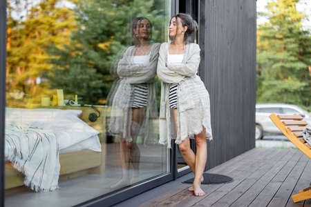 Young woman staying near panoramic window with pine forest view on terrace of wooden modern house. Wellness and mindful resort. Beautiful place for vacation