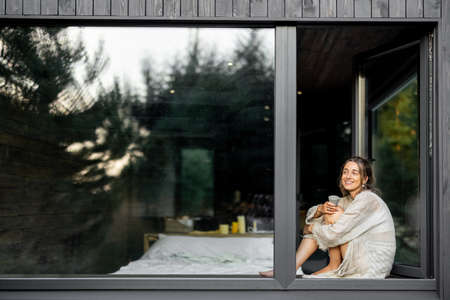 Young woman resting at beautiful country house or hotel, sitting on the window sill enjoying beautiful view on pine forest. View from outside. Concept of solitude and recreation on nature
