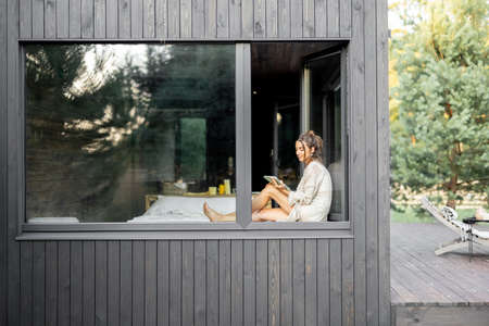 Young woman resting at beautiful country house or hotel, sitting with tablet on the window sill enjoying beautiful view on pine forest. View from outside. Concept of solitude and recreation on nature