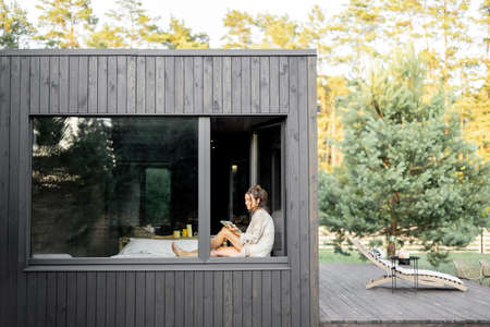 Young woman resting at beautiful country house or hotel, sitting with tablet on the window sill enjoying beautiful view on pine forest. Concept of solitude and recreation on nature.
