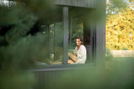 Young woman resting at beautiful country house or hotel, sitting with tablet on the window sill. View from outside. Concept of solitude and recreation on nature. Beautiful destinations for vacation. Foto de archivo