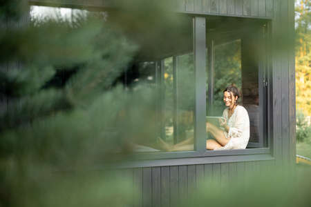 Young woman resting at beautiful country house or hotel, sitting with tablet on the window sill enjoying beautiful view on pine forest. View from outside. Beautiful destinations for vacation