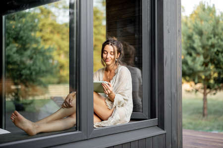 Young woman enjoy of resting at modern house or hotel in pine forest, sitting with tablet on the window sill. Concept of solitude and recreation on nature. Beautiful destinations for vacation