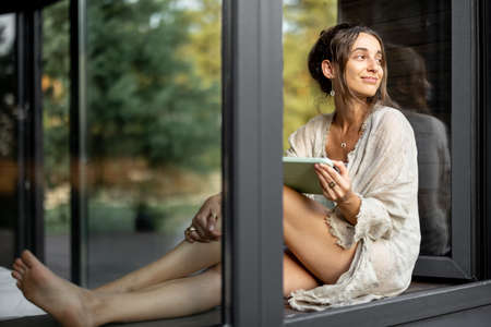 Young cheerful woman enjoy of resting at modern house or hotel, sitting with tablet on the window sill and looking at pine forest. View from outside. Beautiful destinations for vacation Foto de archivo