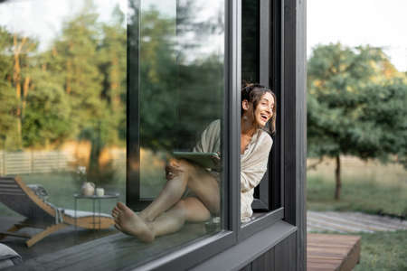 Young woman enjoy of resting at modern house or hotel, sitting with tablet on the window sill and looks out on pine forest. Concept of solitude and recreation on nature