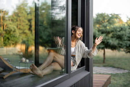 Young woman enjoy of resting at modern house or hotel in pine forest, sitting with tablet on the window sill and greeting someone. Beautiful destinations for vacation Foto de archivo