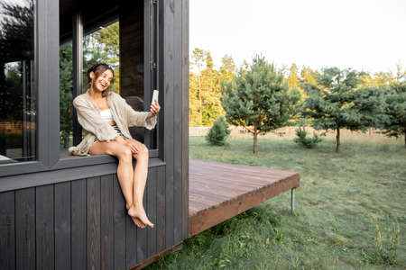 Young woman resting at modern house or hotel in pine forest, sitting on the window dangling her legs outside and making selfie. Beautiful destinations for vacation. Copy space
