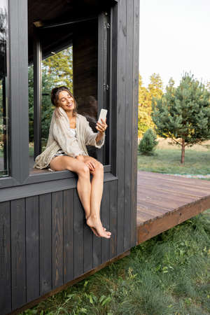 Young woman resting at modern black house or hotel in pine forest, sitting on the window dangling her legs outside and making selfie. Concept of solitude and recreation on nature