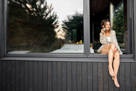 Young woman resting at modern house or hotel in pine forest, sitting on the window dangling her legs outside and enjoying calmness and quietness. Beautiful destinations for vacation. Copy space