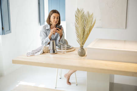 Young woman using cell phone at home, relaxing and having leisure time at modern bright apartment