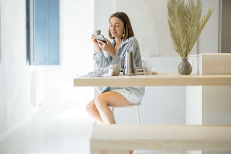 Young woman using cell phone at home, relaxing and having leisure time at modern bright apartment. Home comfort and breakfast at home