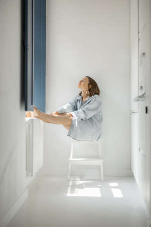 Young woman sitting alone by the window in a bright room at home. Self-isolation, loneliness, girl feeling calm and relaxed at home