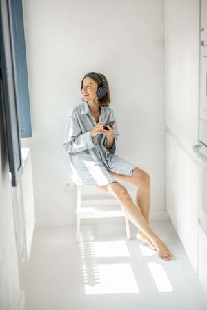 Young woman enjoys music in headphones while sitting alone in a bright room at home. Self-isolation and loneliness concept