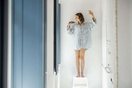 Young woman wakes up in the morning enjoying music in headphones in a bright room by the window at home. Self-isolation and good morning concept