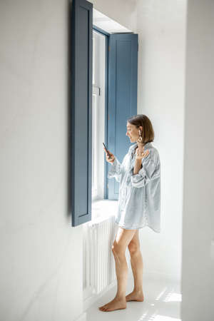 Young woman dressed freely communicate by phone with a headset having a video call at home. Remote work and communication. Self-isolation at comfortable home