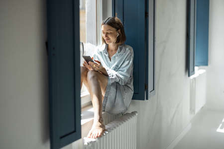 Young woman listening to a music or talking on phone while sitting on the widow sill at home. Remote work and communication. Self-isolation at comfortable home