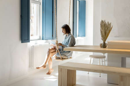 Woman having a leisure time, reading book and sitting on a swing in a bright room. Self-isolation and rest at comfortable home