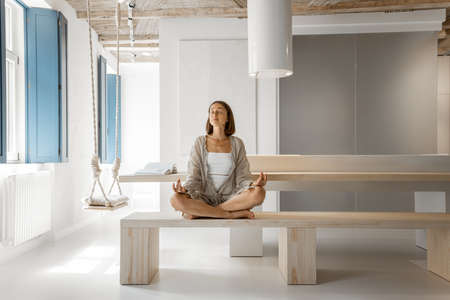 Young woman meditates sitting on a bench in a modern studio apartment. Home coziness, self-isolation and comfort