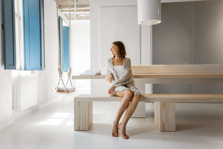 Young woman sitting relaxed on a wooden bench in a modern studio apartment. Home coziness, self-isolation and comfort at home concept