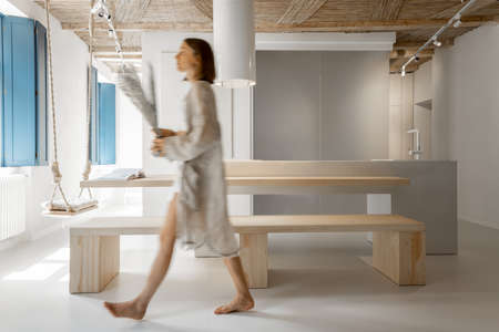 Modern studio apartment interior with motion blurred female person walking, decorating home. Home coziness, self-isolation and comfort at home concept Foto de archivo