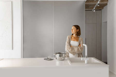 Portrait of a young woman standing in the modern white kitchen interior. Home comfort, lifestyle at home, modern and stylish interior