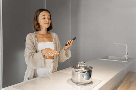 Young stylish woman cooking on induction hob at modern kitchen. Concept of smart technologies of kitchen appliances