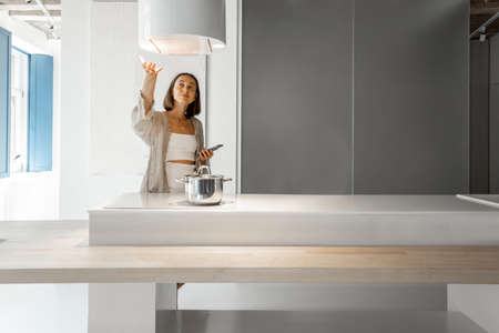 Young woman controls hood, while standing with cell phone and cooking at modern kitchen. Concept of smart technologies of kitchen appliances Foto de archivo