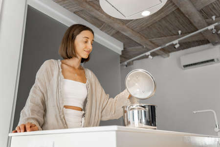 Young woman boiling food on electric hob, cooking at modern kitchen at home. Home comfort, lifestyle at home, eating at home