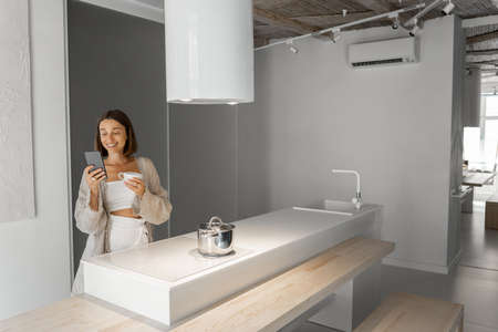 Woman with coffee cup and cell phone at modern kitchen interior in the morning Foto de archivo