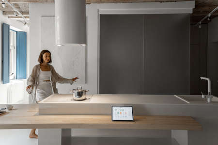Woman cooking at modern kitchen interior, digital tablet with running smart home application at the table. Concept of smart home and smart kitchen appliances