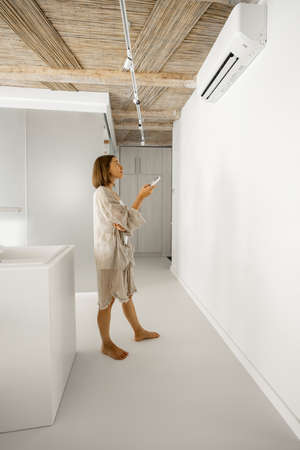 Woman sets the temperature on the air conditioner with remote control, while standing at modern white kitchen of the studio apartment
