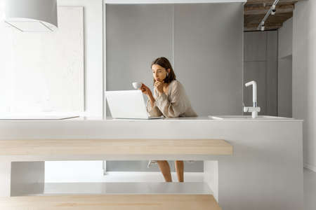 Young woman works on a laptop, standing by the kitchen table at modern and bright studio apartment. Working from home concept Foto de archivo
