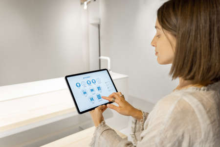 Young woman controls smart kitchen appliances with a digital tablet while standing at modern kitchen at home. Mobile device with running program