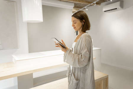 Young woman communicates by digital tablet with a headset having a video call at home. Remote work and communication. Self-isolation at comfortable home Foto de archivo