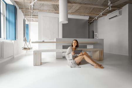 Young woman works on a digital tablet while sitting relaxed on the floor at modern studio apartment. Remote work from comfortable and modern home concept