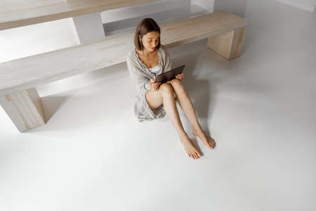 Young woman works on a digital tablet while sitting relaxed on the white floor at home. Remote work from home concept
