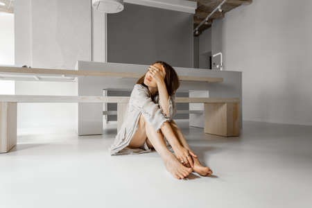 Young sad woman sitting depressed alone at home. Self-isolation and quarantine during a pandemic