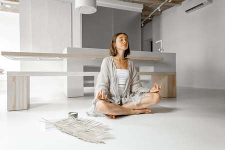 Woman meditating at home sitting in lotus position on the floor in modern studio apartment. Concept of calm and comfort at home