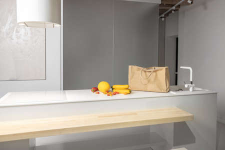 Healthy food ingredients and shopping bag on the table at kitchen. Raw yellow fruits and vegetables ready to cook