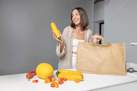 Young woman takes fresh food ingredients out of the bag, preparing for the cooking healthy food at modern kitchen. Eating healthy at home