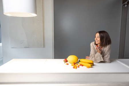 Young woman with yellow fruits and vegetables by the kitchen table at home. Healthy eating at modern kitchen Foto de archivo