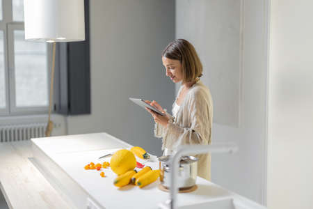 Young woman cooking healthy vegetarian food and using digital tablet at modern kitchen inteiror. Modern and healthy lifestyle in a comfortable home