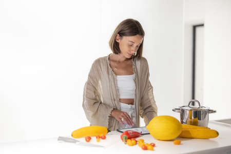 Woman cooking vegetarian food from fresh yellow vegetables, looking at the recipe on a digital tablet at modern kitchen