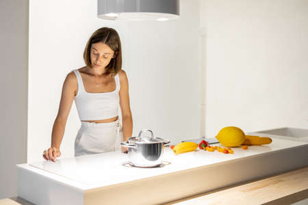 Young woman cooking vegetarian food from fresh food ingredients at kitchen. Modern and healthy lifestyle in a comfortable home