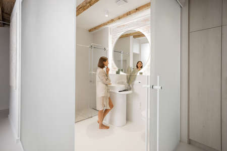 Lifestyle portrait of a woman at modern and bright bathroom interior. Woman feeling well being at comfortable home Foto de archivo