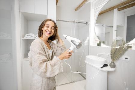 Woman dries hair with a hair dryer in a modern bathroom Foto de archivo