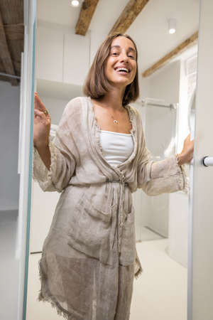 Portrait of a cheerful young woman opening the bathroom door at modern studio apartment. Person feeling comfortable and cozy at home Foto de archivo