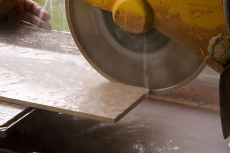 Water lubricated tile saw cutting a tile Imagens