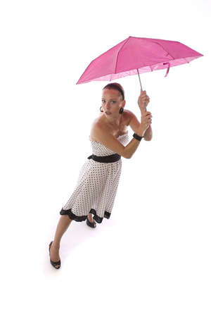 Young woman in a polka dot dress, holding a pink umbrella
